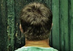 back view of a man standing in front of a green fence and focused in on his hair
