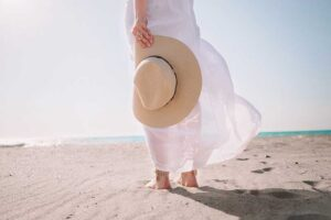 woman standing on the beach with a hat